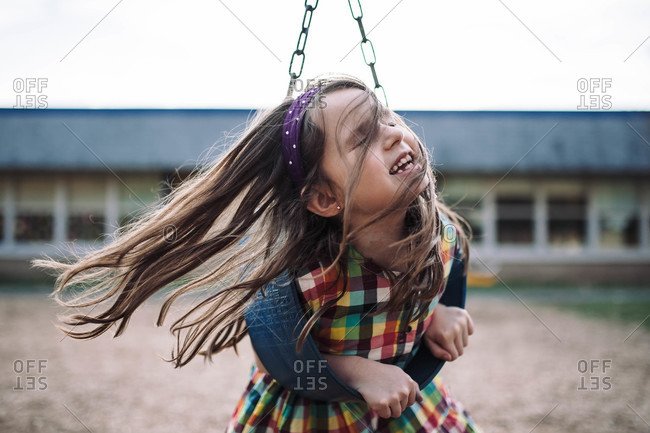 Girl with windblown hair playing on a swing
