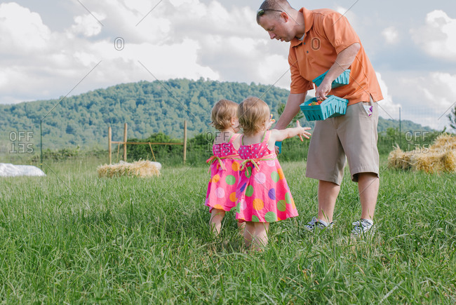 Father with his twin daughters at a berry farm