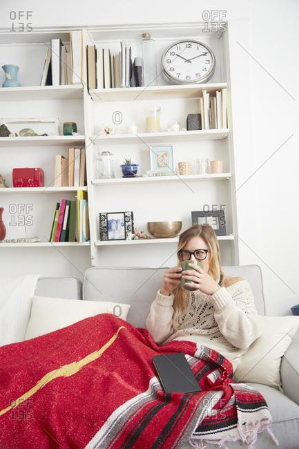 Young female holding mug on the sofa