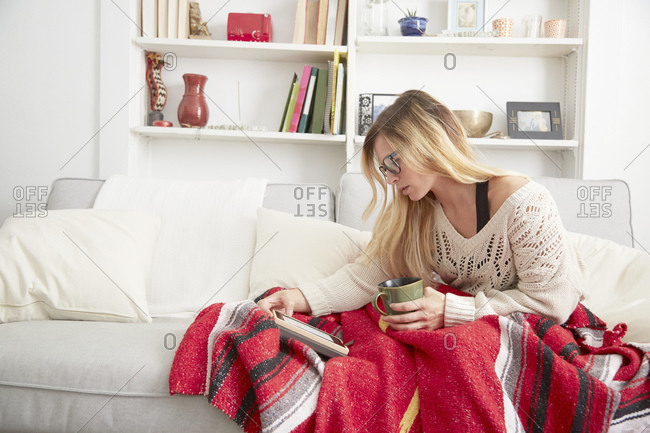 Woman in glasses reading tablet on the sofa