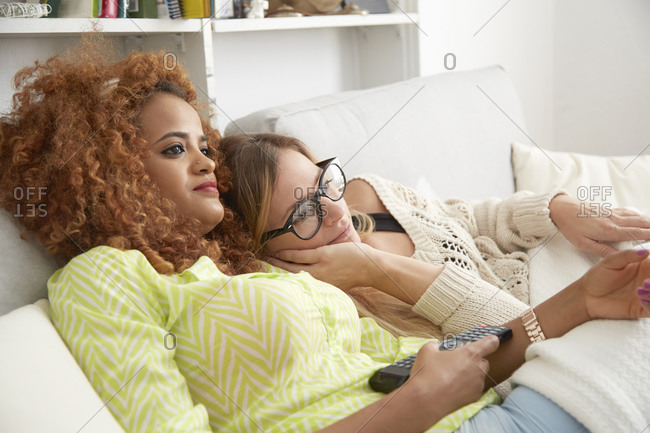 Two young females relaxing on couch
