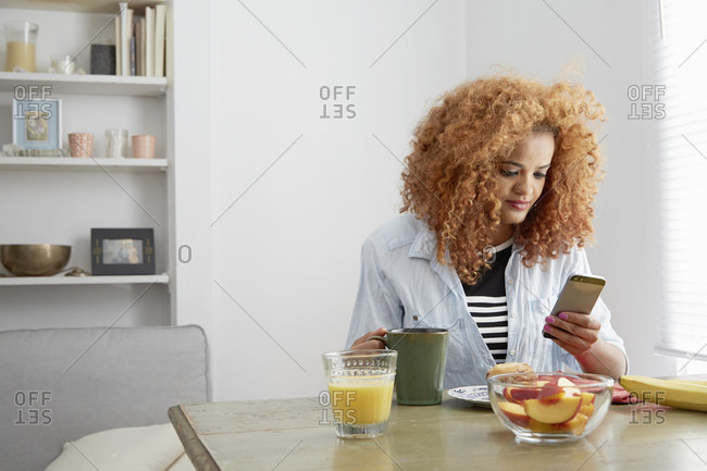 Young woman using cell phone while having breakfast