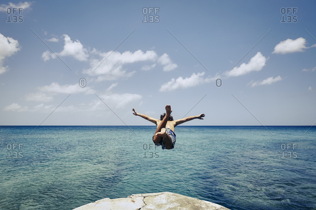 Young man jumping off a rock doing a swan dive into the ocean