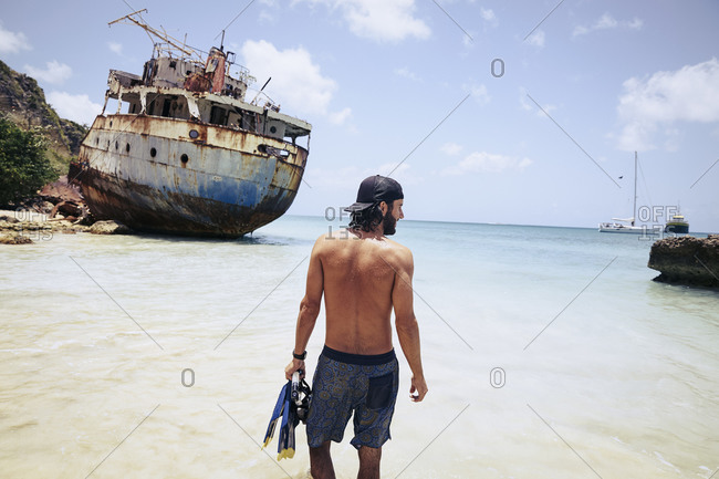 Young man holding snorkeling gear standing on the beach in front of a shipwreck