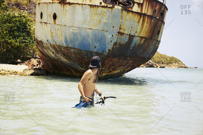 Young man wading in the water of the ocean while holding snorkeling gear and looking back at a shipwreck