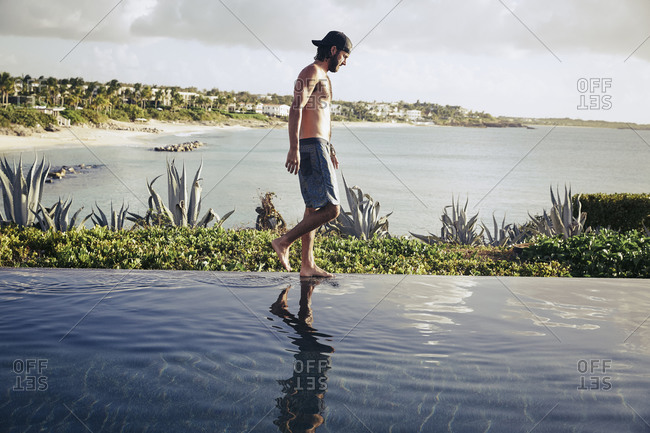 Young man walking in the water at the edge of a pool overlooking the ocean
