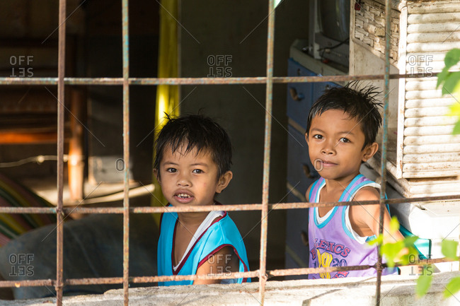 Ronda, Philippines - January 6, 2016: Two young boys smiling through window in Philippines