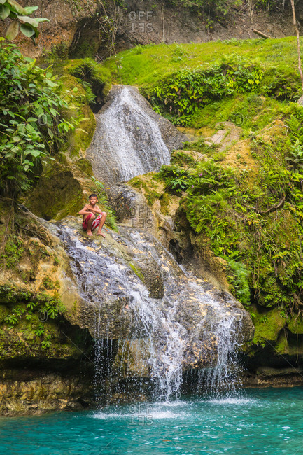 Moalboal, Philippines - January 7, 2016: Boy sitting on Kawasan Falls in the Philippines