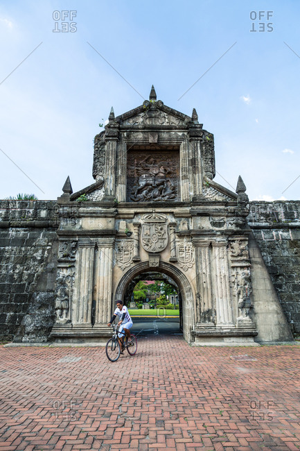 Manila, Philippines - December 23, 2015: Man riding bicycle through the gate at Fort Santiago, Manila, Philippines