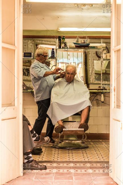 Tavira, Portugal - October 27, 2014: Barber cutting a man's hair in a barbershop in Tavira, Portugal