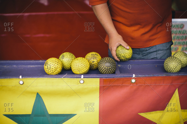 Boy picking up rubber balls to play a carnival game