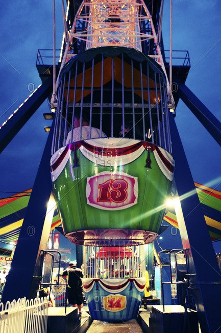 People riding in a carnival bucket ride at dusk