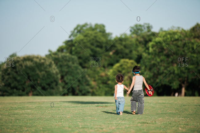 Two little boys holding hands and playing in a field