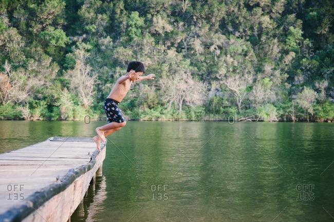 Little boy jumping off of a dock