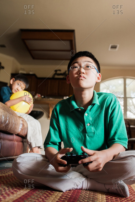 Boy watches his older brother play video game