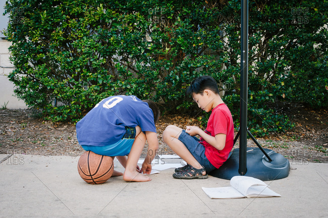 Boys sitting with papers at basketball hoop in driveway