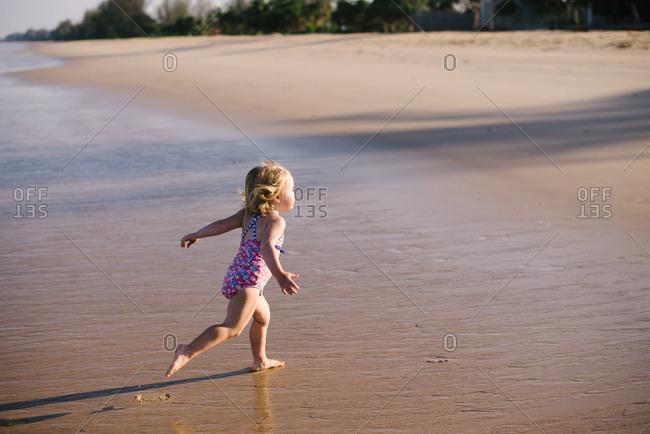 Girl running away from ocean