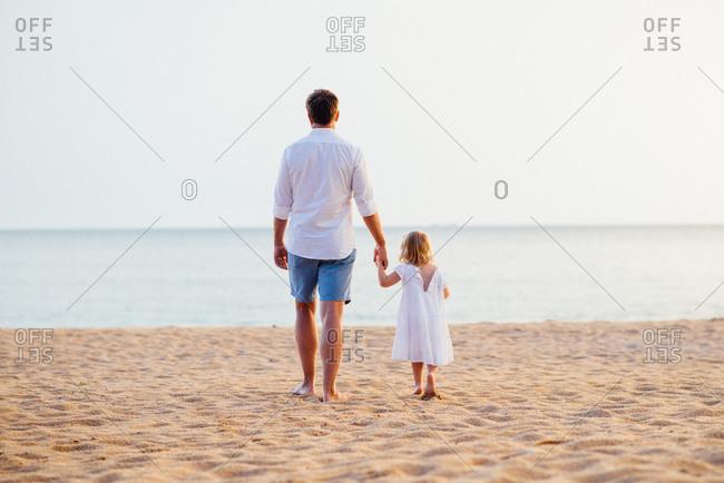 Dad holding girl's hand on beach