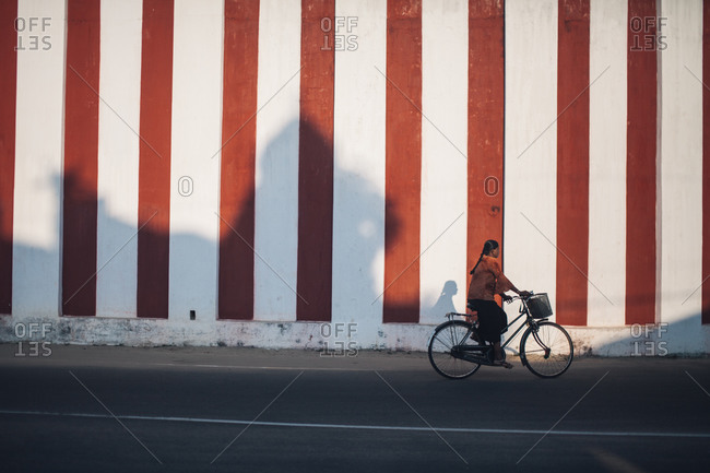 Sri Lanka - March 19, 2016: Woman on bike with shadows on wall