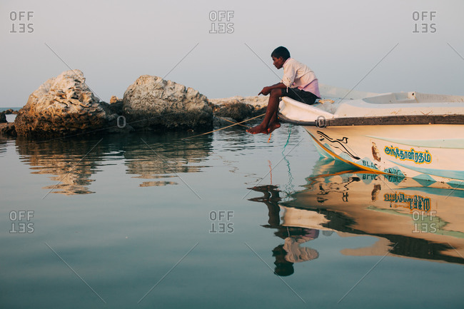 Sri Lanka - March 22, 2016: Man resting on front of boat