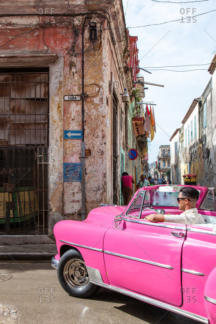 March 18, 2016 - Cuba:  Young man driving a classic pink convertible