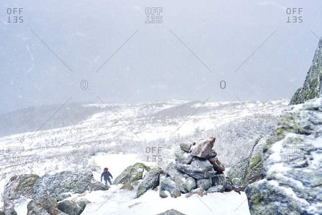 Hiker climbing a snowy mountainside in New Hampshire