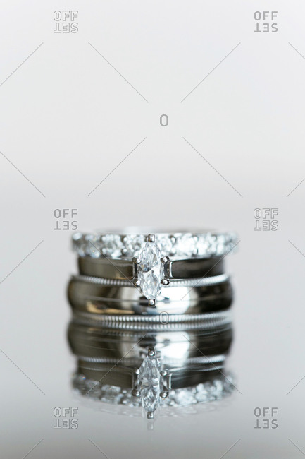 Stack of three wedding rings on a reflective surface