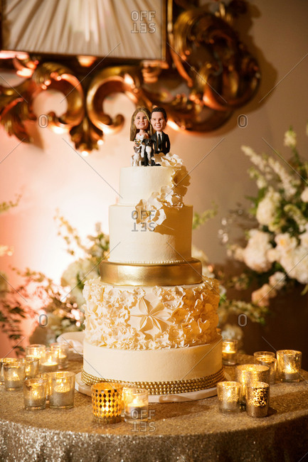 Gold decorated wedding cake with a topper with bride, groom and dogs