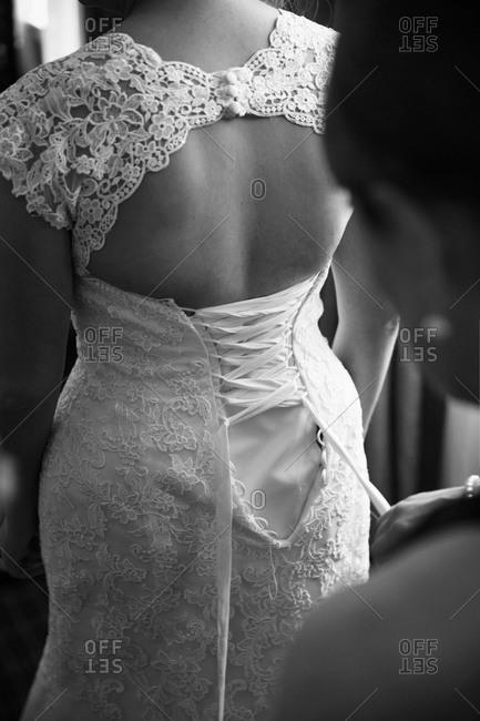 Woman lacing a corset of a bride's dress