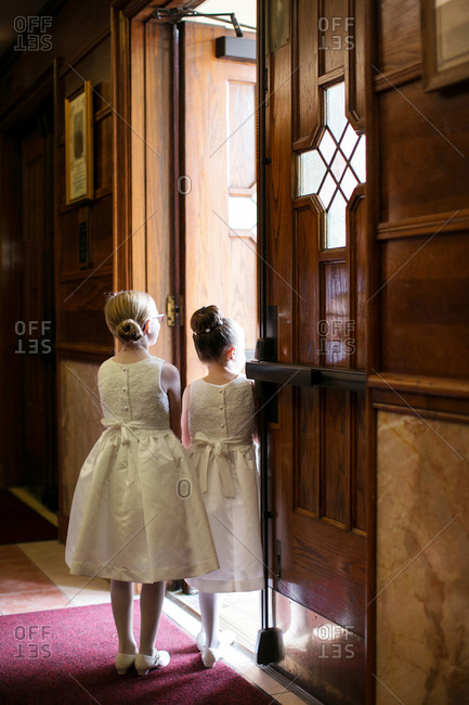 Back view of two flower girls waiting at a doorway