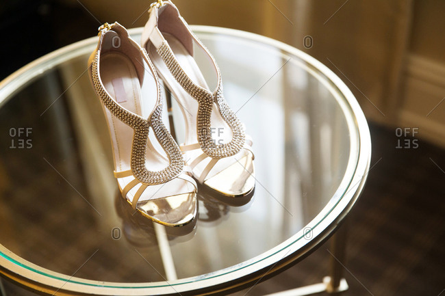 High-heeled shoes on a round glass table