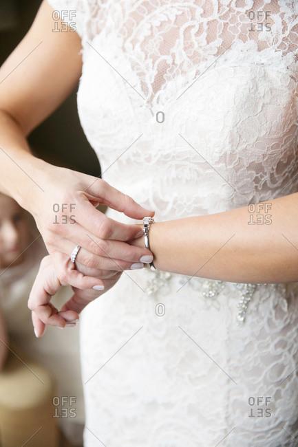 Bride adjusting clasp on bracelet