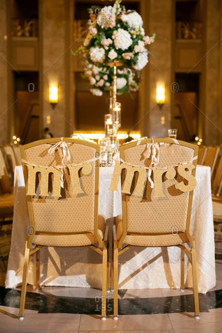 Two chairs at a wedding table decorated with banners reading 'Mr' and 'Mrs'