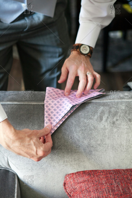 Man folding a colorful pocket square