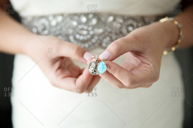 Bride holding two Catholic patron saint charms