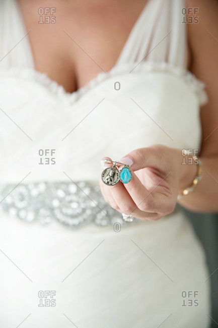 Bride holding two Catholic patron saint charms