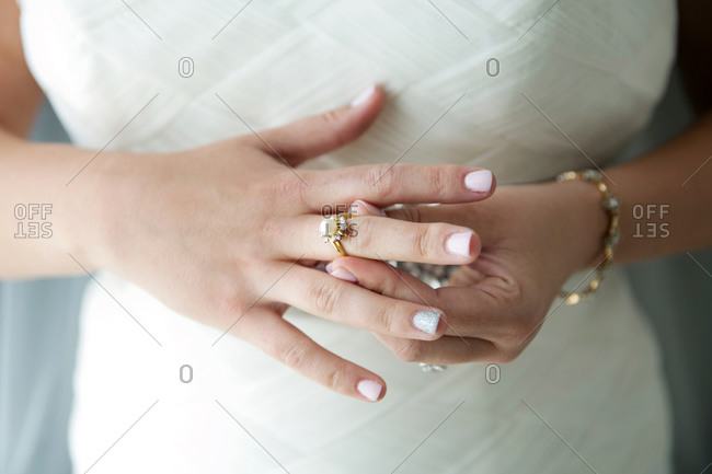 Close-up of a bride adjusting a pearl ring on her finger