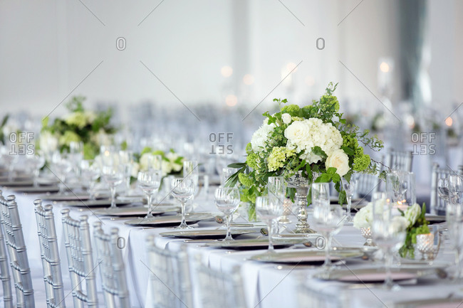 Long table set with flowers in a bright, airy wedding hall