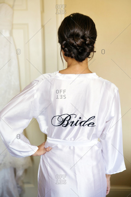 Young woman wearing a robe with the word bride