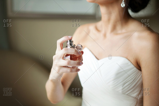 Bride spraying her neck with perfume