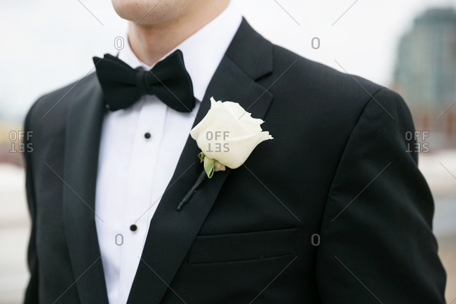 Groom wearing a tuxedo with a white rose on his lapel