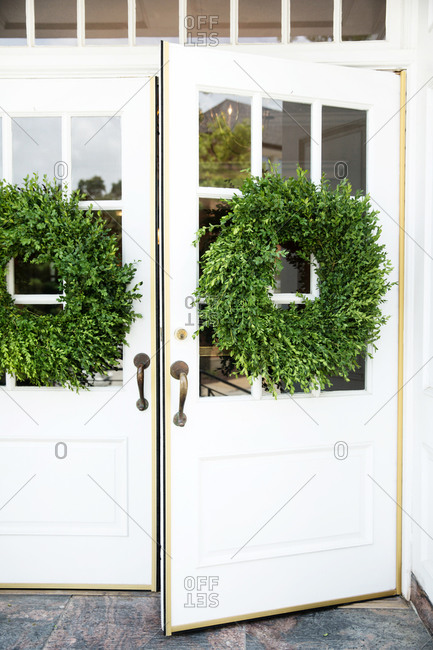 White entrance doors decorated with fresh green wreaths
