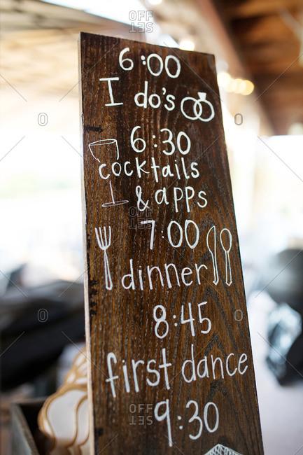 Wedding reception schedule written on a wooden board