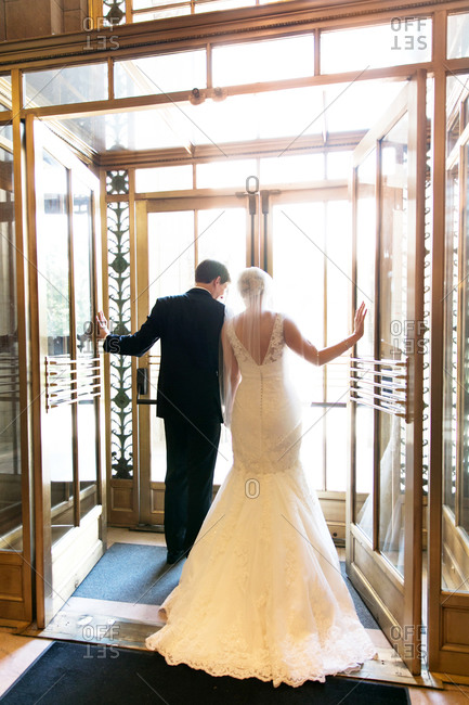 Newlywed couple walking out of an elegant lobby entrance
