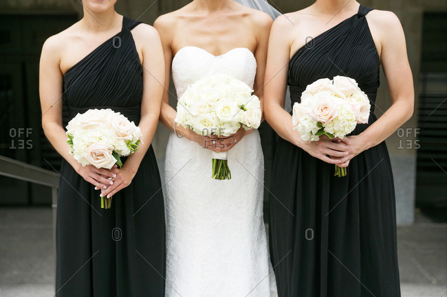 Bride standing between two bridesmaids in black dresses