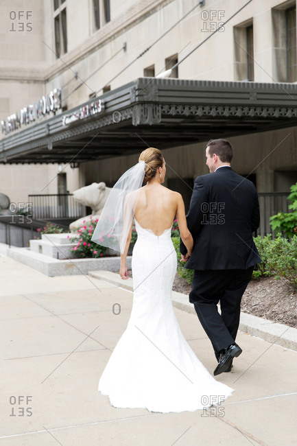 Newlyweds holding hands and walking toward the entrance of an elegant building