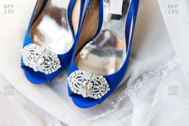 Open toe blue satin shoes on a wedding veil