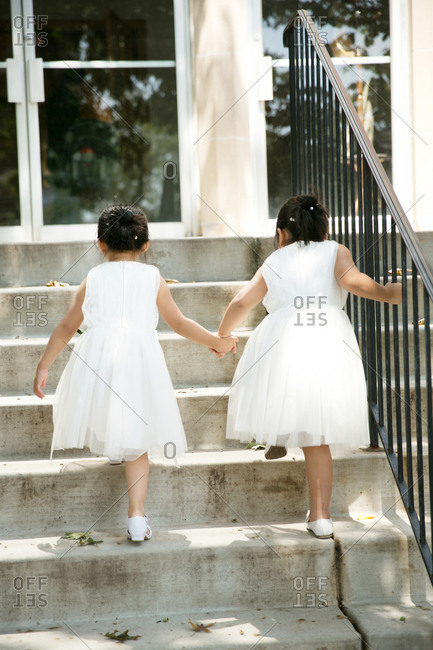 Flower girls holding hands and walking up steps