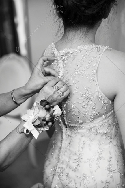 Woman helping a bride fasten the back of her wedding gown