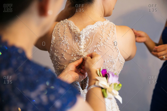 Woman fastening the back of a bride's wedding gown